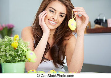 Smiling female laughing with colorful easter eggs - a...