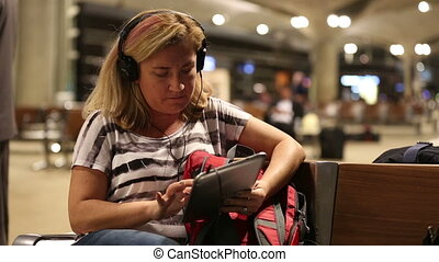 passenger waiting in airport - middle age blonde women using...