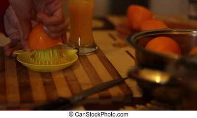 Manual Orange Squeeze - An orange is squeezed by hadn for...