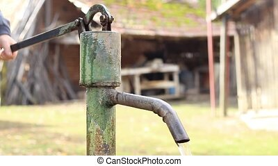Mechanical Water Pump - Man swings the hand and pump tof...