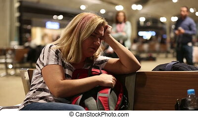 passenger waiting in airport - middle age tired blonde woman...