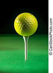 Golf Ball on Tee - A yellow golf ball positioned on top of a...