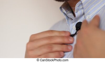 Mounting Lavalier Microphone - Before an interview, a man...