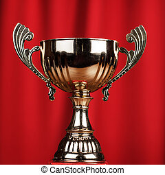 golden trophy cup over red background - golden trophy cup on...