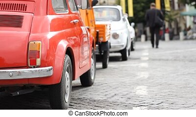 People Passing Retro Cars - People are walking near some old...