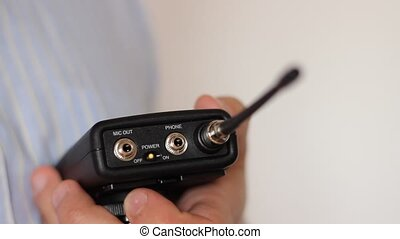 Power On Lavalier Microphone Transm - Man starts a lavalier...