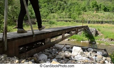Person is Crossing a Footbridge - A woman crosses a small...