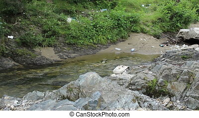 Pollution on River Shore - Mountain river`s bank are full of...