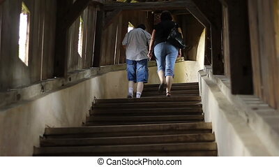 People Climbing Wooden Stairs - In the warm light of the...
