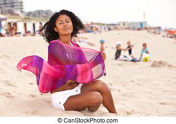Beautiful brazilian woman sitting on the beach