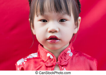 China girl in traditional Chinese red Tang suit greeting