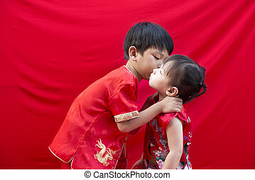 China boy and girl in traditional Chinese red Tang suit...