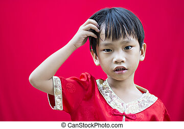 China boy in traditional Chinese red Tang suit greeting