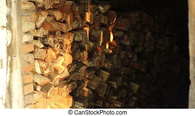 Shadows Play on Logs - On the firewood logs sunlight gently...