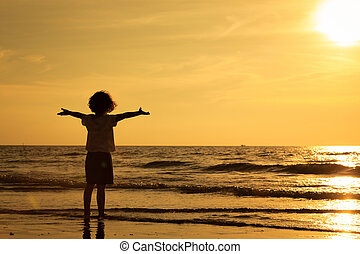 Happy little boy standing on the beach at the sunset time