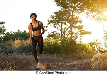 Young african american woman jogging in nature - Full length...