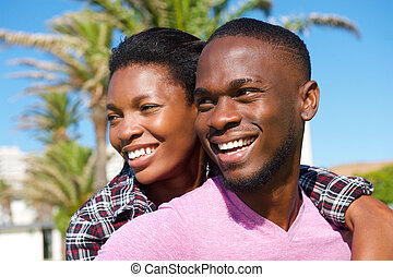 Cheerful young african american couple smiling outdoors -...