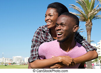 Happy young man carrying attractive girlfriend on his back