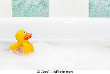 Rubber duck in foam bath - Cute rubber duck floating in suds...