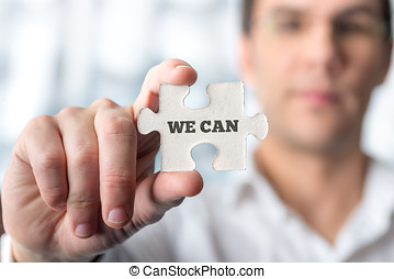 Businessman holding puzzle piece with We can text in a...