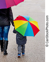 mother and child with umbrella, a symbol of solidarity,...