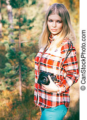Young Woman walking with retro photo camera outdoor...
