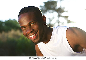 Happy young black man smiling outdoors - Close up portrait...