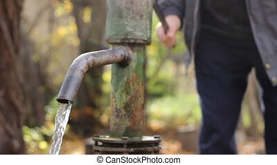 Using Hand Well Pump - Fresh water flows down the barrel of...