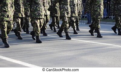 Troops Marching - Soldiers in camouflage uniform and wearing...