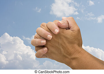 Praying  - Two hands on a sky background, praying