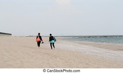 Two Girls Walking on Beach - Two girls with coloured bags...