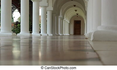 White Piling Corridor - Steps on a hallway with arches along...
