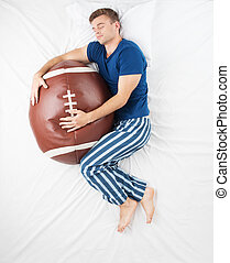 Man sleeping with soft ball toy - Top view photo of young...