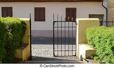 Woman Exits Yard Throught Iron Gate - A girl with red shirt...