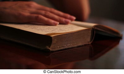 Woman Searches an Old Book - On a warm pale light a woman...