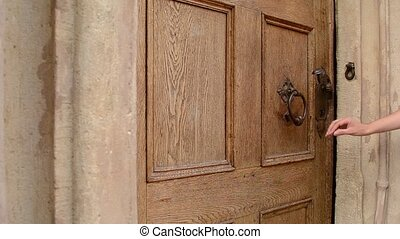 Woman Uses Door Knocker - A woman knocks on wood made old...