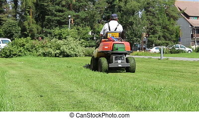 "Worker Driving Lawn Mower - ""A gardener driving a lawnmower..."