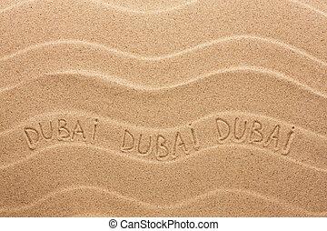 Dubai inscription on the wavy sand, as background
