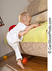 Sofa assault - Little boy in white is climbing on sofa