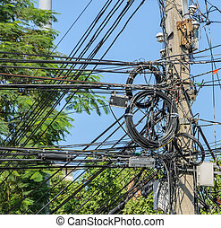 Messy electric cables on pole in Bangkok, Thailand -...