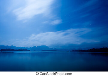 Lake in night - Stars in the blue sky. Below is the peaceful...