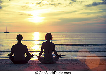 Silhouette of young man and woman practicing yoga in the...