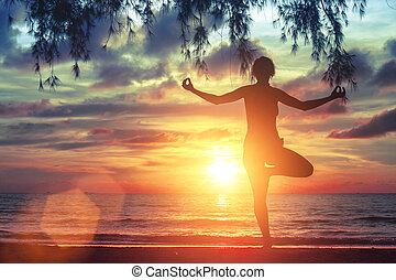 Young yoga girl practicing on the ocean beach at amazing...