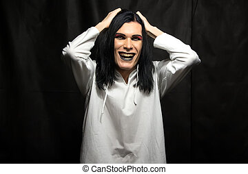 Photo of mad man with grin on black background