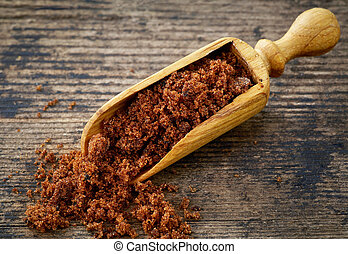 muscovado sugar - scoop of muscovado sugar on old wooden...