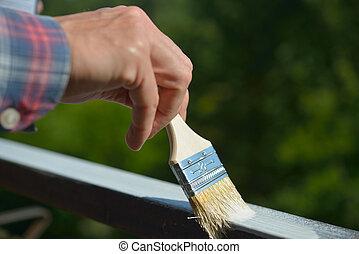Man painting a guardrail - Man painting a guard rail on a...