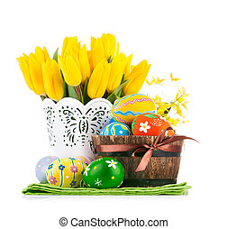 Easter eggs in basket with yellow tulips. Isolated on white...
