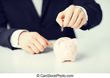 man putting coin into small piggy bank - picture of man...