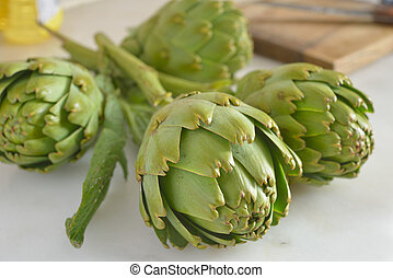 Artichokes - Four raw artichokes on a marble table