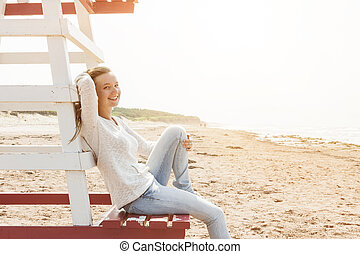 Young woman sitting on beach lifeguard chair - Young smiling...